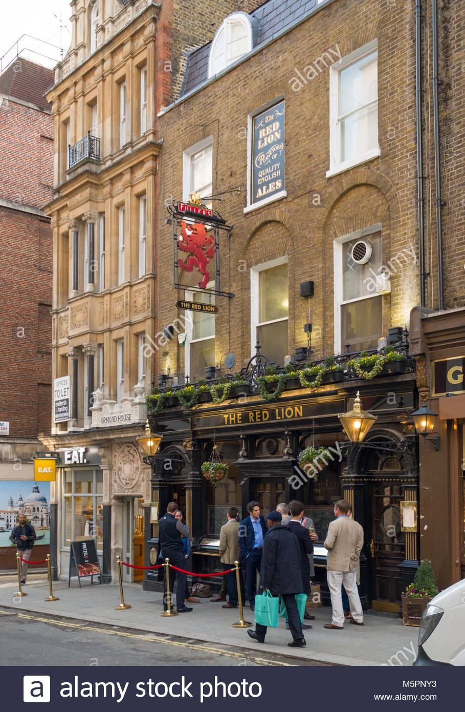 Men standing outside the Red Lion pub drinking beer, Duke of York Street, St. James's, City of Westminster, - Stock Image