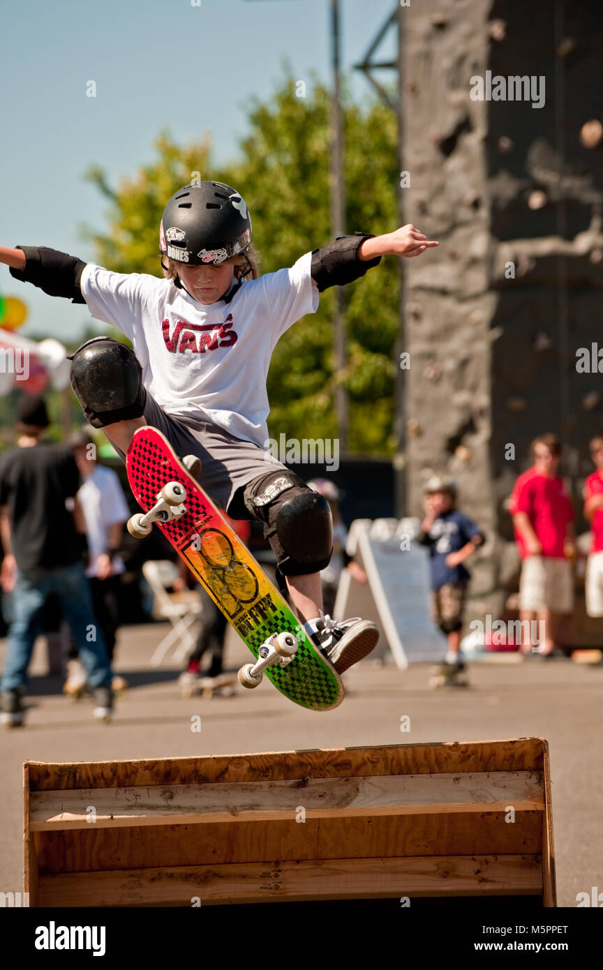 Boy with helmet on skate board airborne over a ramp - Stock Image