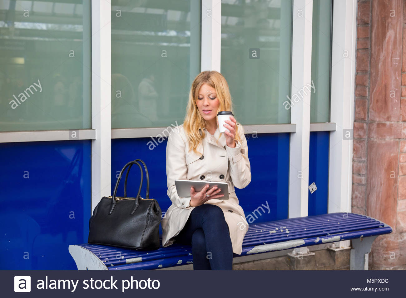 Young woman sitting waiting on a bench waiting for train - Stock Image