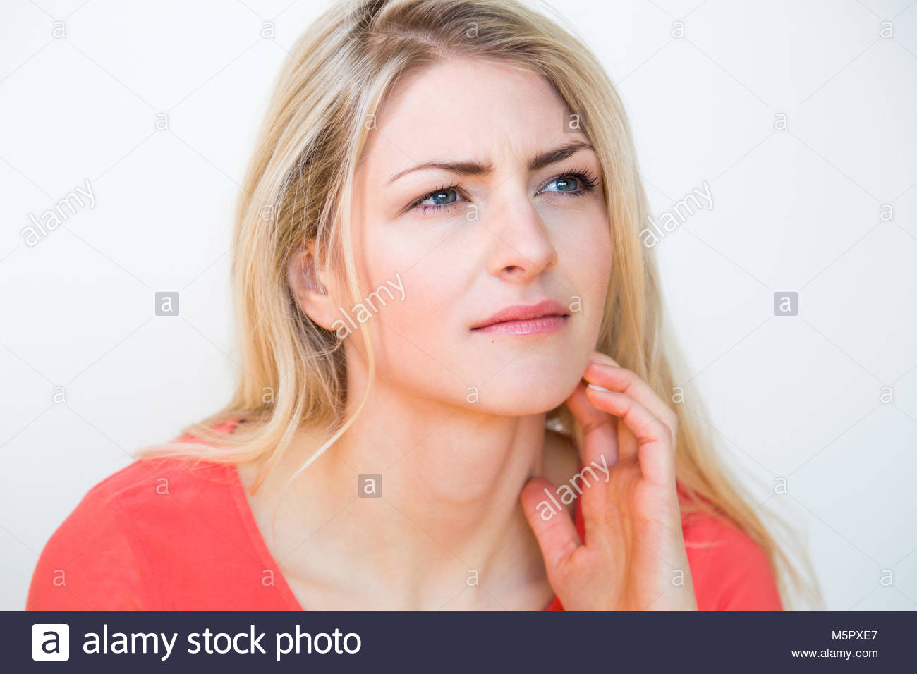 Young Woman with Hand in Hair Looking Perplexed - Stock Image