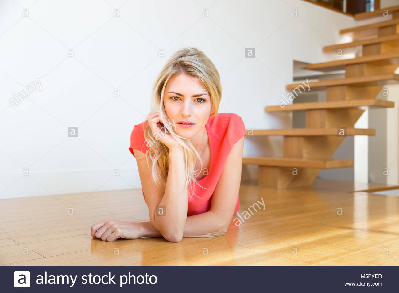 Confident Young Blond Woman Lying on Wooden Floor - Stock Image