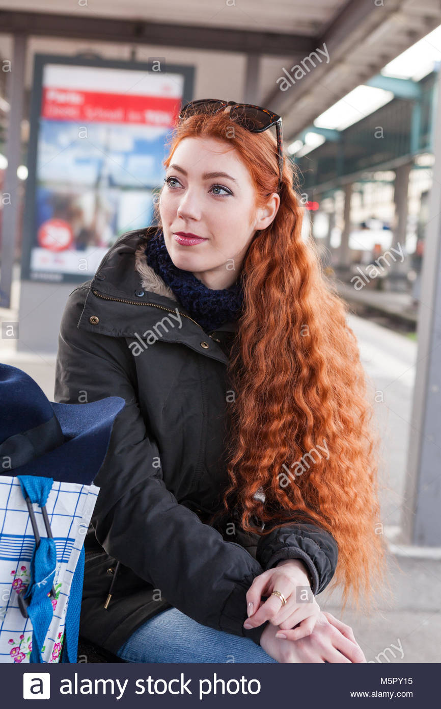 Red headed young woman waiting for the train - Stock Image