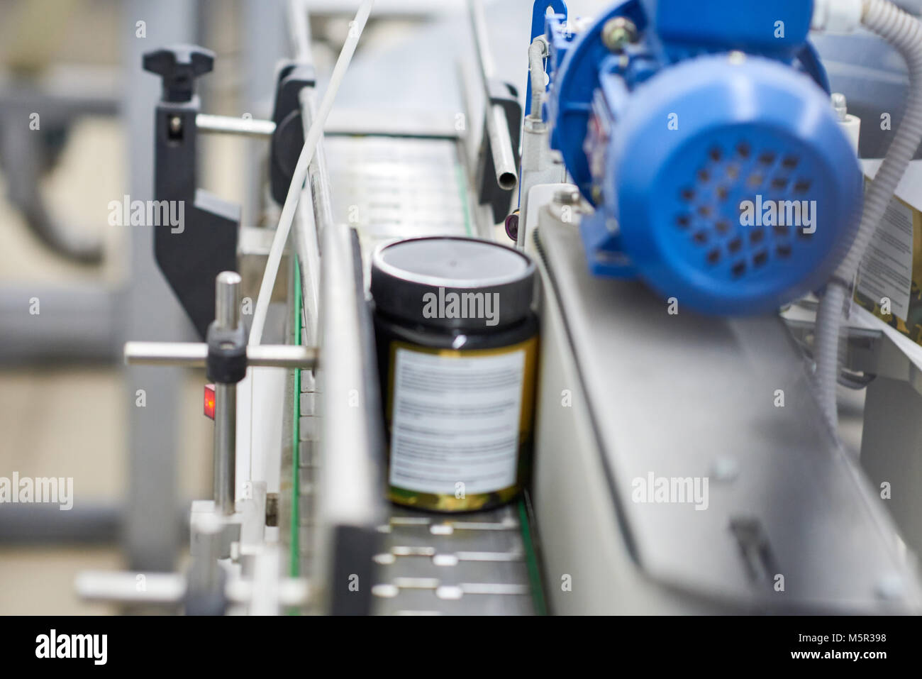 Close-up shot of pill bottle moving along conveyor line of modern pharmaceutical factory, blurred background - Stock Image