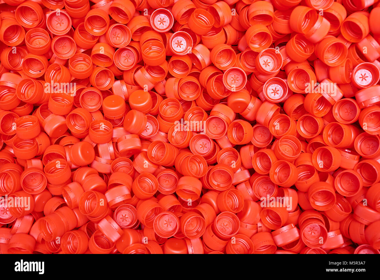 Composition with red plastic bottle caps illuminated with sunbeams, close-up shot - Stock Image