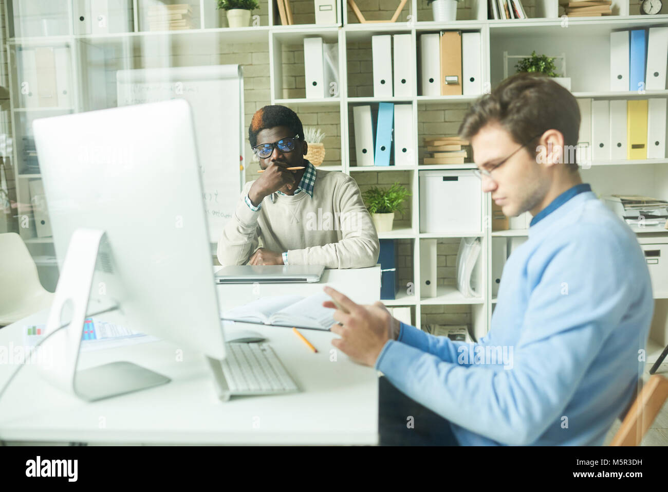 Working process in modern open plan office: multi-ethnic team of white collar workers sitting at desks and working - Stock Image