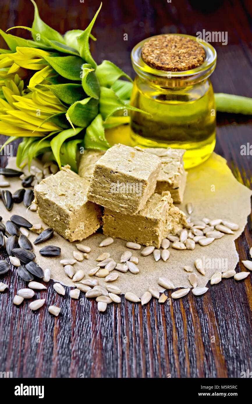 Eastern sweetness halva sunflower on paper, sunflower seeds, oil and flower on a background of a wooden board - Stock Image