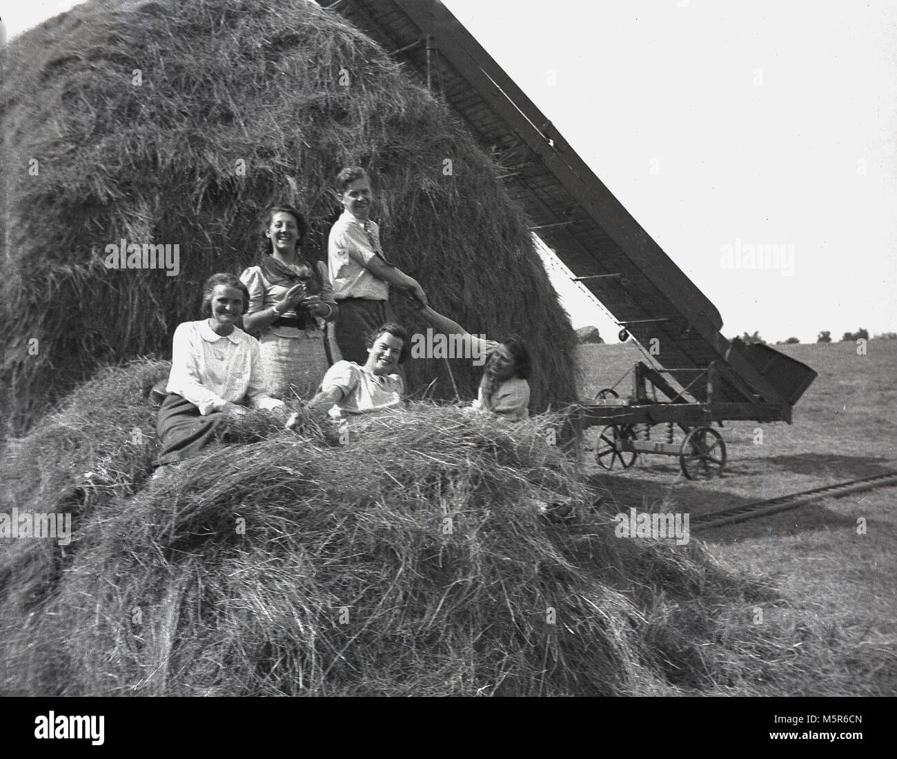 1937, historical picture, family enoying a rural holiday in the fresh air of Devon, England, having fun on a haystack Stock Photo