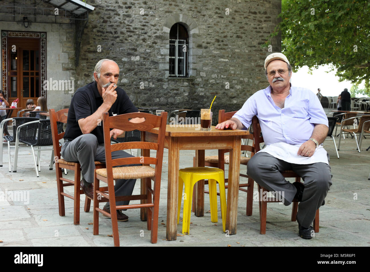 The coffee shop owner sits down for a coffee with a friend in the main square of Kypseli village, Tzoumerka, Epirus. - Stock Image