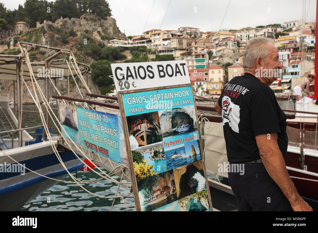 The captain of the boat tour to Paxos, Antipaxos and the blue caves is waiting for the tourists to go on board.Parga, - Stock Image