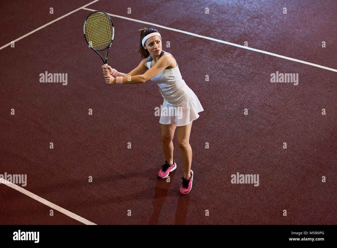 High angle portrait of forceful woman playing tennis in indoor court swinging racket, copy space - Stock Image