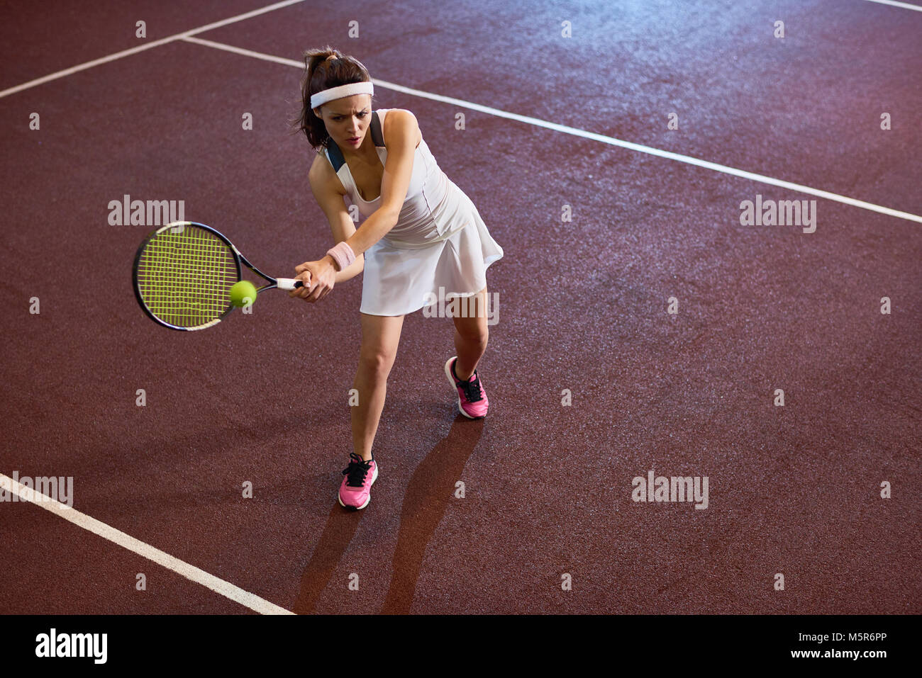 High angle full length  portrait of forceful woman playing tennis in indoor court, copy space - Stock Image