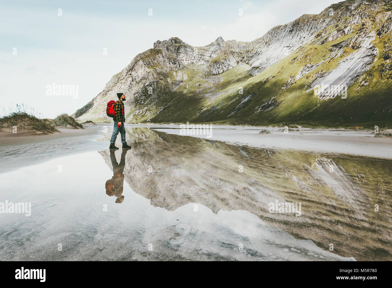 Man walking alone at sandy beach in mountains Travel lifestyle emotional concept adventure outdoor summer vacations - Stock Image