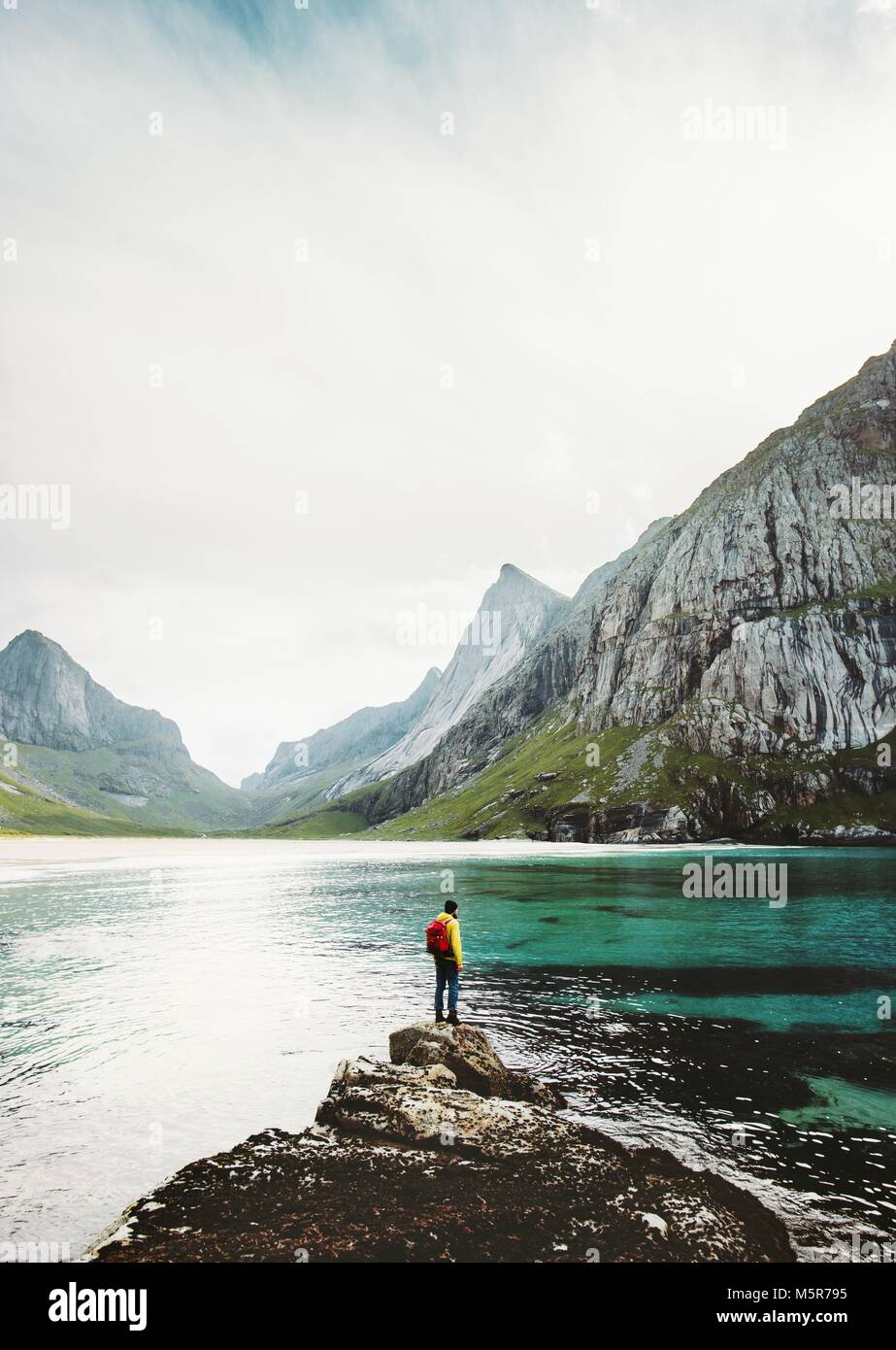 Man backpacker standing alone at sea stone in Norway Travel lifestyle survival emotional concept adventure outdoor - Stock Image