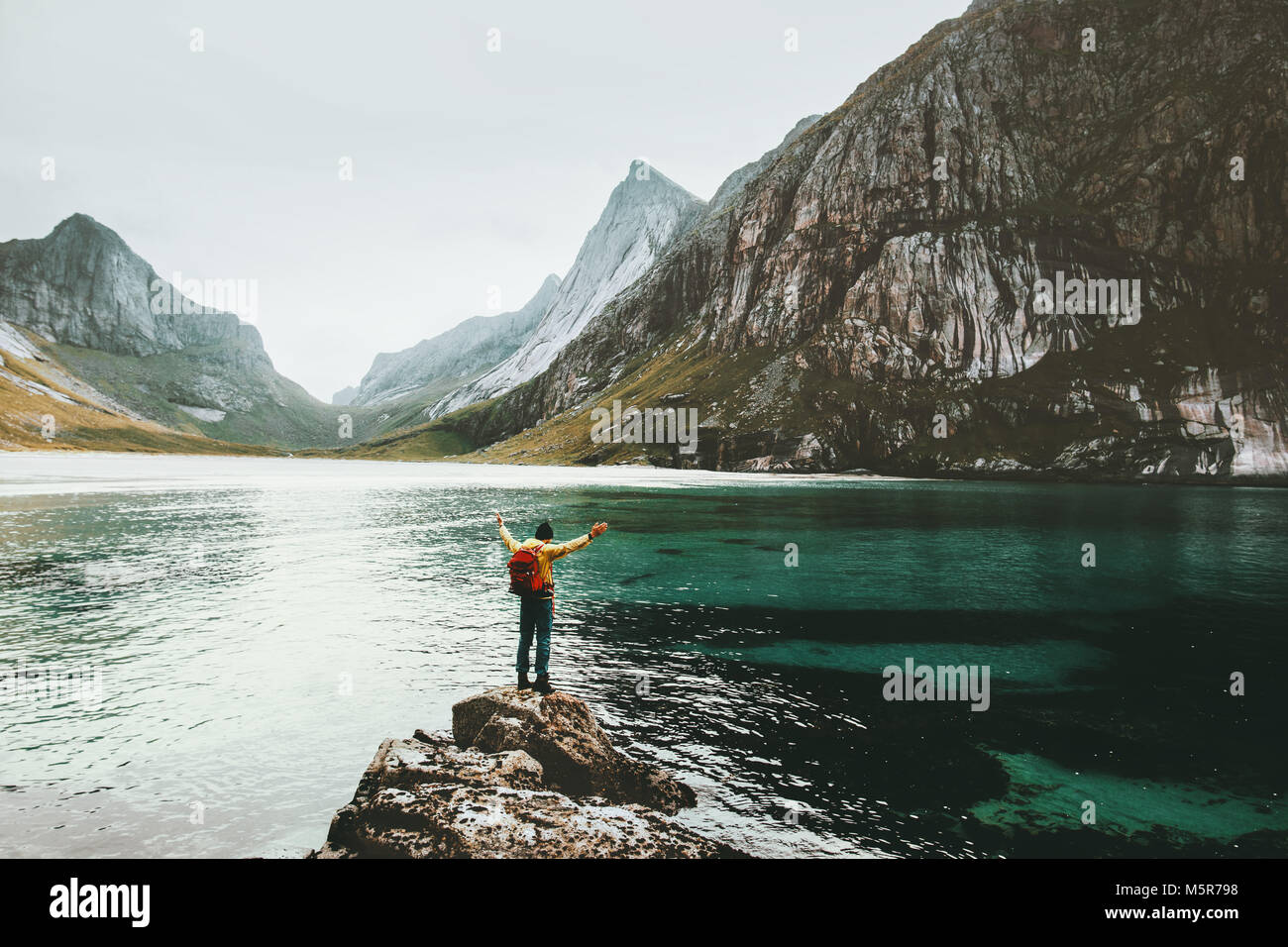 Traveler Man raised hands standing alone at sea stone Travel lifestyle survival emotional concept adventure outdoor - Stock Image