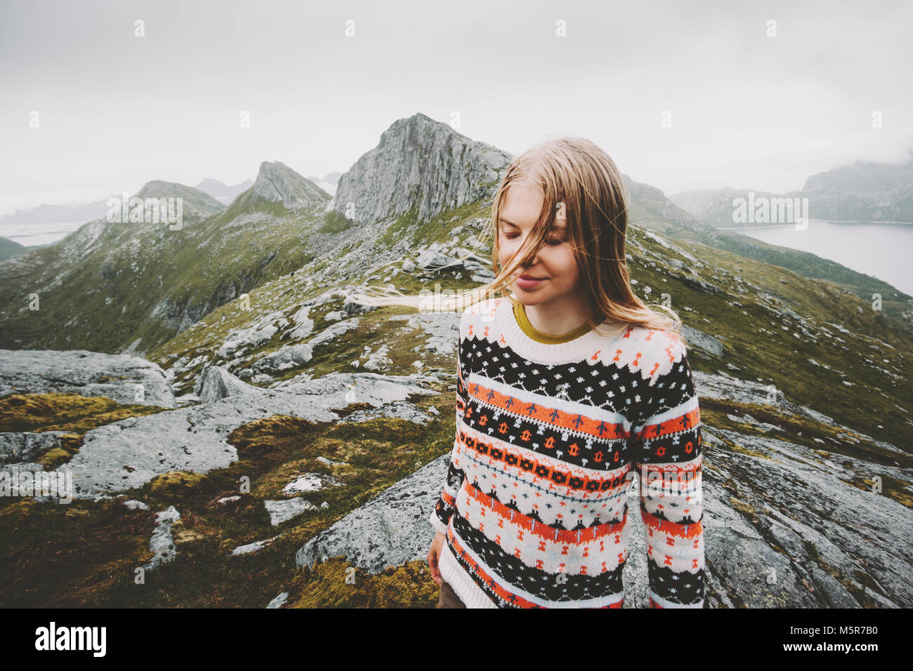 Young blonde woman walking in Norway mountains Travel lifestyle emotional concept adventure outdoor summer vacations - Stock Image