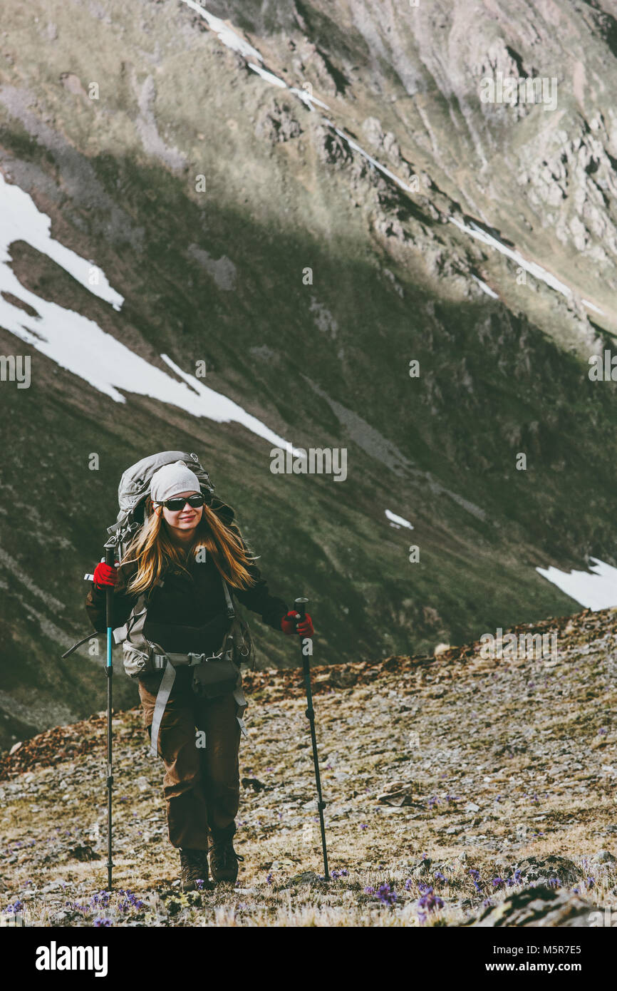 Young woman with backpack on hike in mountains Travel healthy lifestyle adventure concept active summer vacations - Stock Image