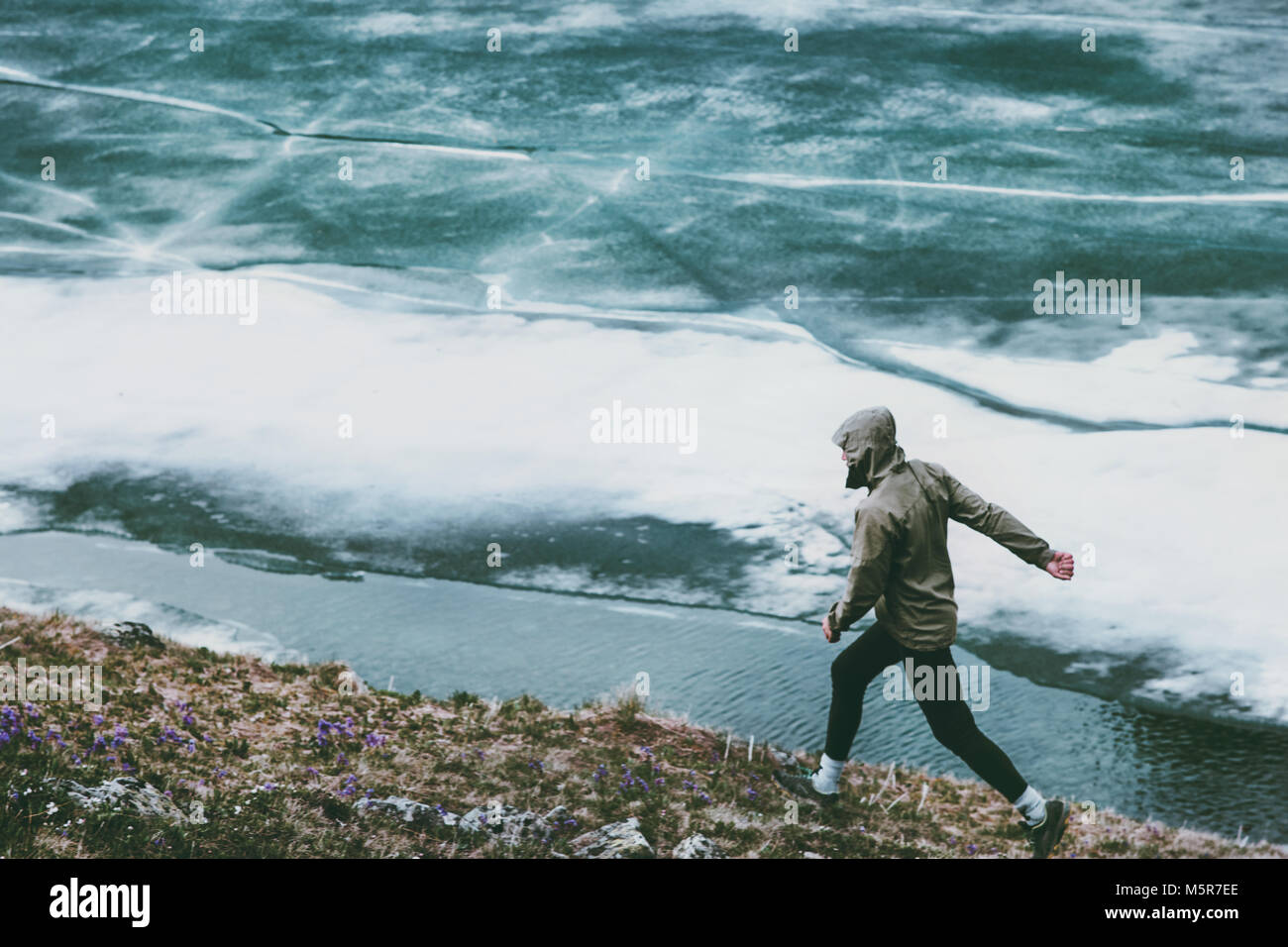 Active Man running at frozen lake Travel adventure healthy lifestyle concept vacations athletic person sport - Stock Image