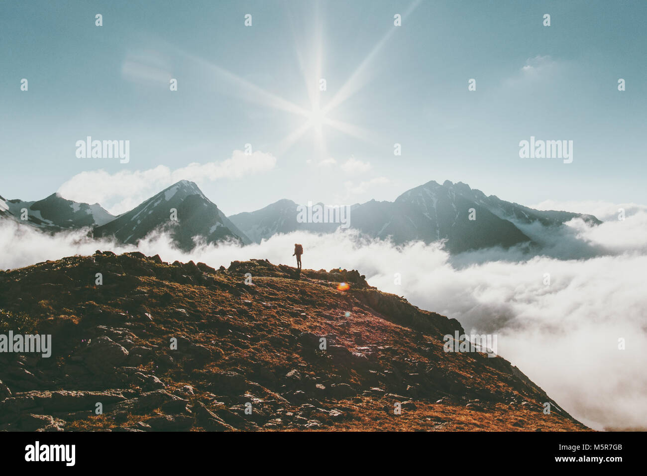 Mountains landscape Travel lifestyle adventure concept traveler standing alone summer vacations outdoor sunny day - Stock Image