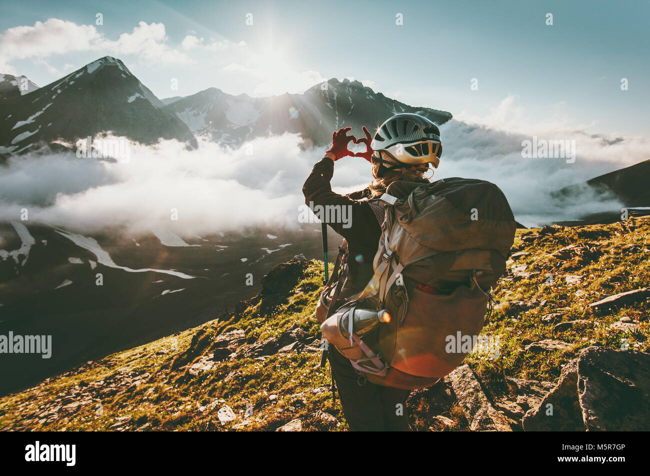 Backpacker woman hands showing heart shape enjoying mountains clouds landscape Travel lifestyle adventure concept - Stock Image
