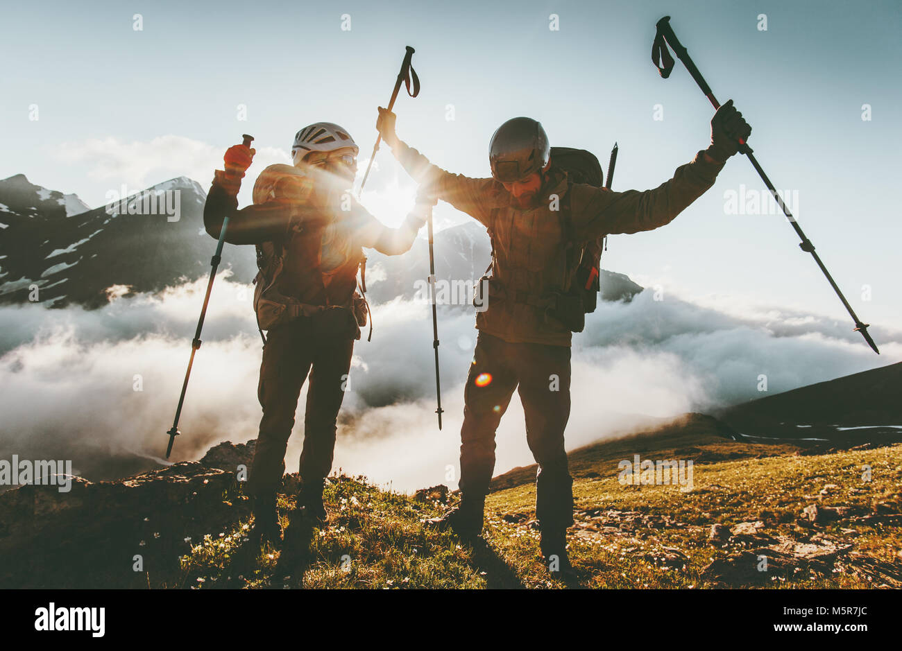 Happy travel couple man and woman on mountain summit love and adventure hiking Lifestyle wanderlust concept sunset - Stock Image