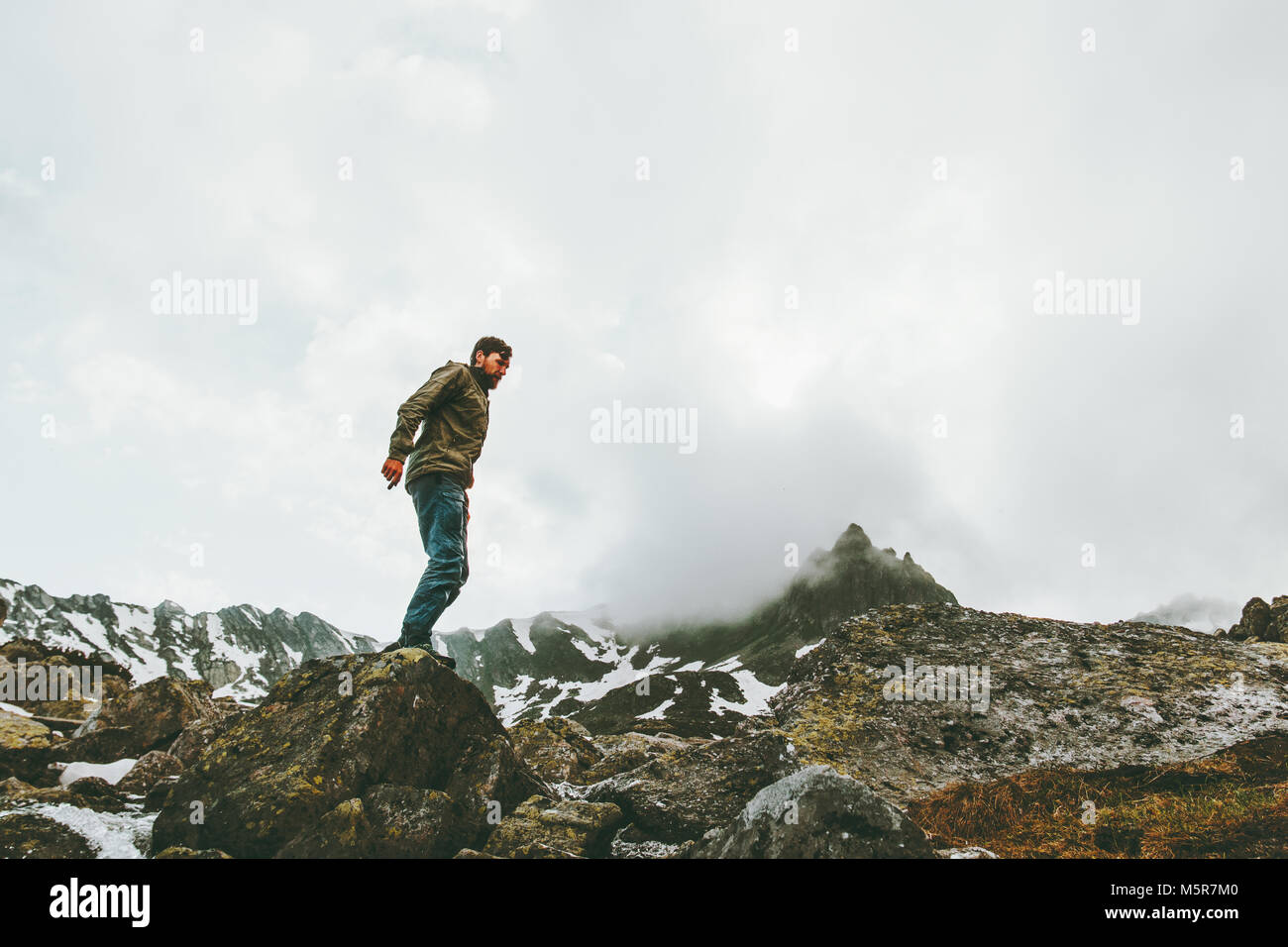 Traveler Man standing alone at foggy mountains Travel lifestyle survival emotional concept adventure outdoor active - Stock Image