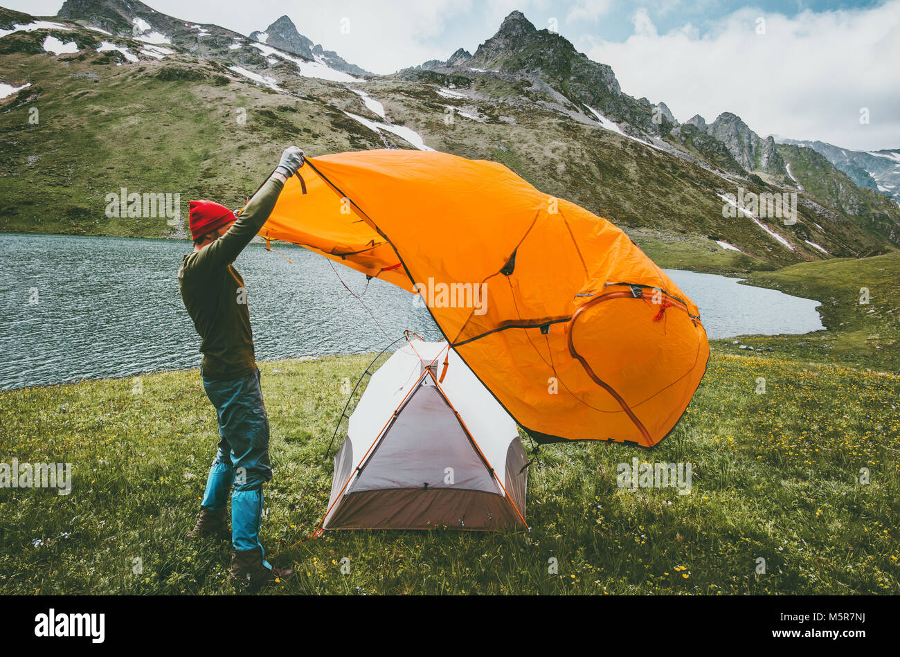 Man pitching tent camping outdoor Travel adventure lifestyle concept mountains journey vacations into the wild - Stock Image