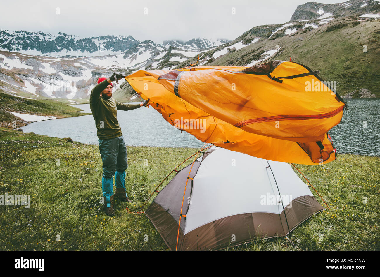 Man adventurer pitching tent camping gear outdoor Travel survival lifestyle concept summer trip vacations in mountains - Stock Image