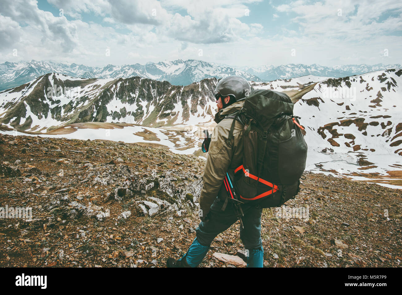 Man traveler with big backpack hiking in mountains expedition Travel survival lifestyle concept adventure outdoor - Stock Image