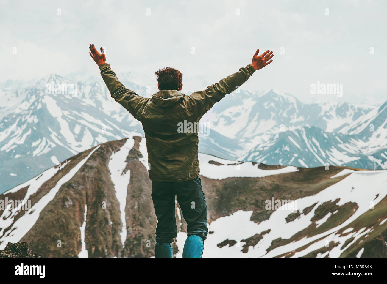 Happy adventurer Man raised hands on summit Travel Lifestyle concept traveler enjoying mountains landscape outdoor - Stock Image