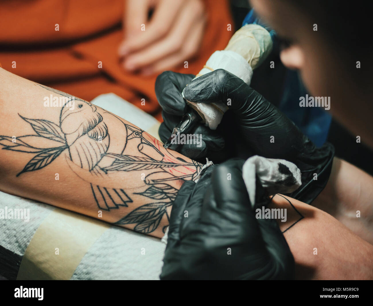 201b0f4b2 Tattoo artist at work. Woman in black latex glove tattooing a young man's  hand with