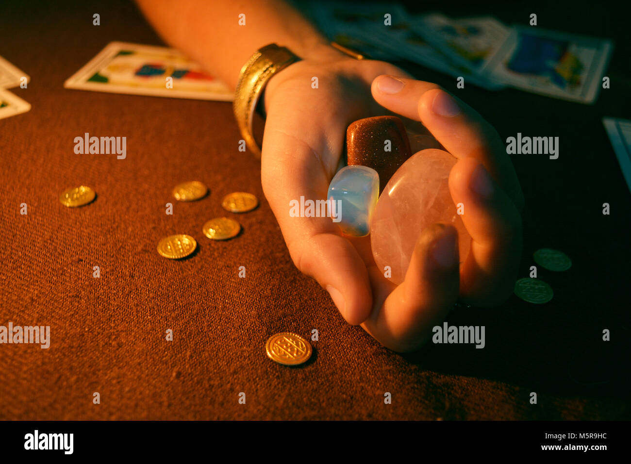 Holding crystals and gold on hand tarot table - Stock Image