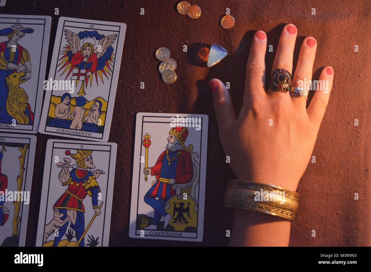 Tarot table and hand with crystals and gold - Stock Image