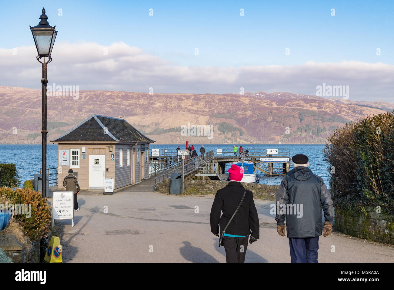 Luss - tourists walking towards the pier and Loch Lomond in winter - Stock Image