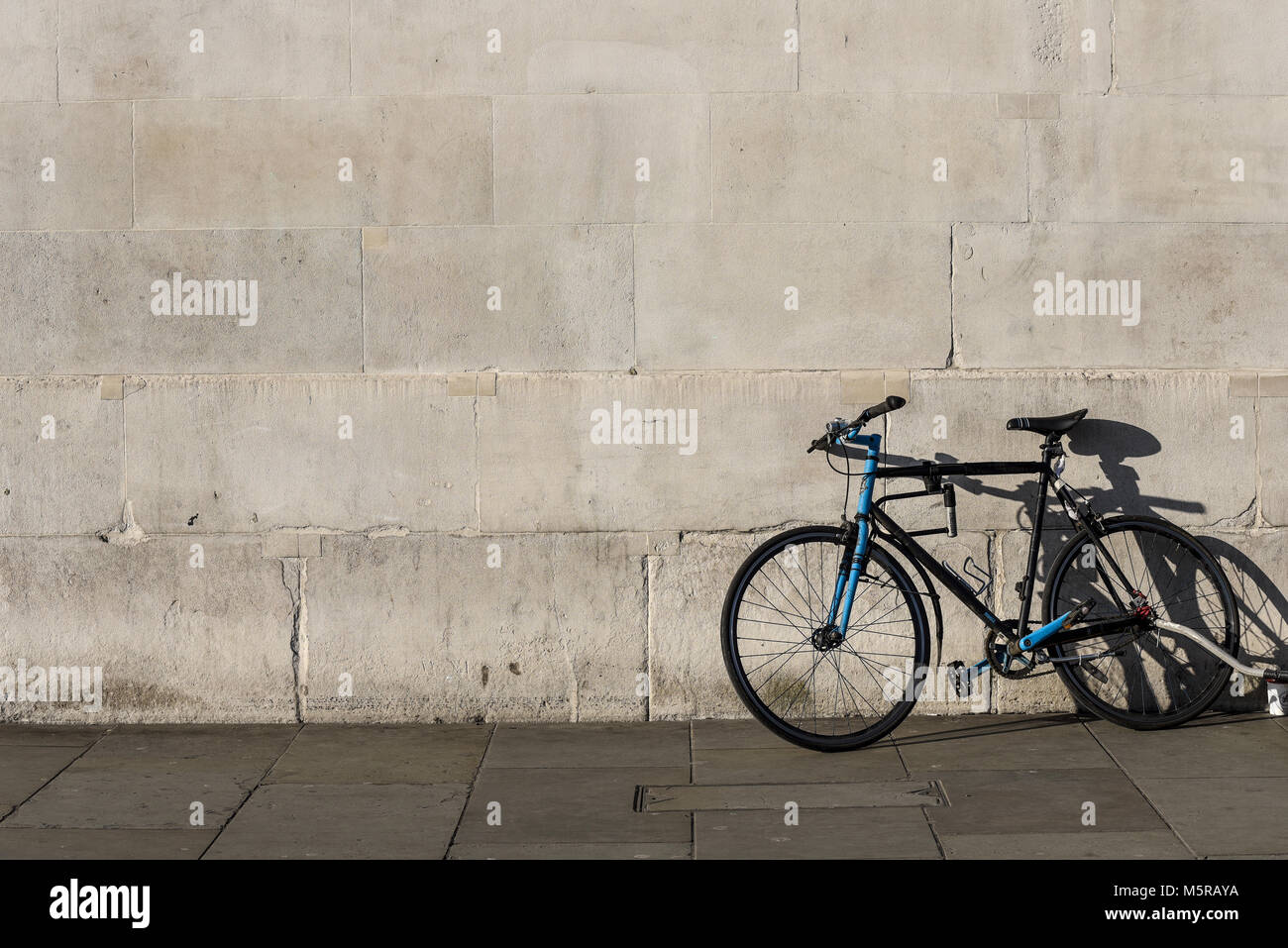 Bicycle against a blank plain wall. Large space for copy. Plain background. Cycle. Bike. Sunny day - Stock Image