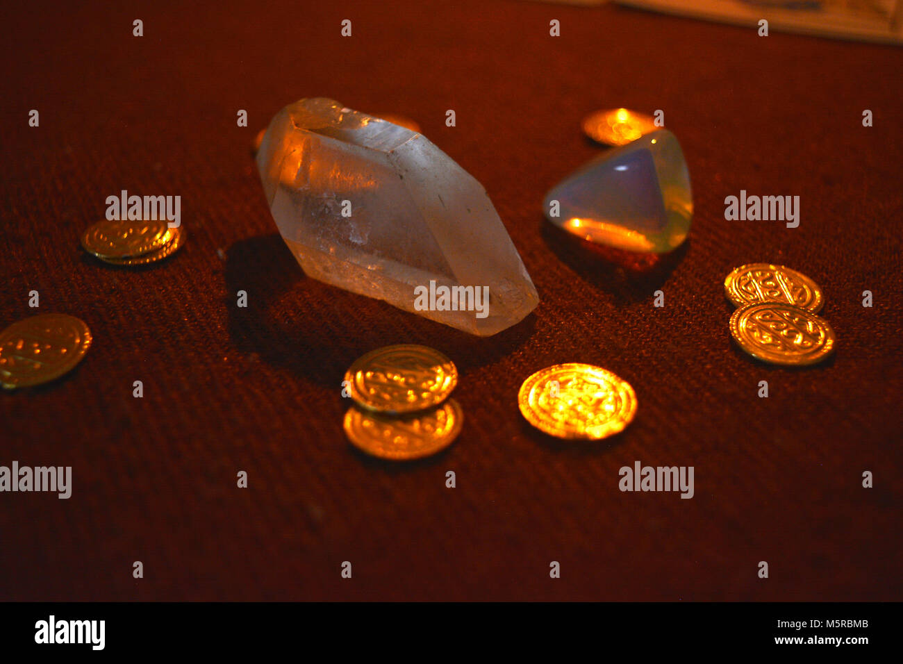 Crystals and gold on table by candle light - Stock Image