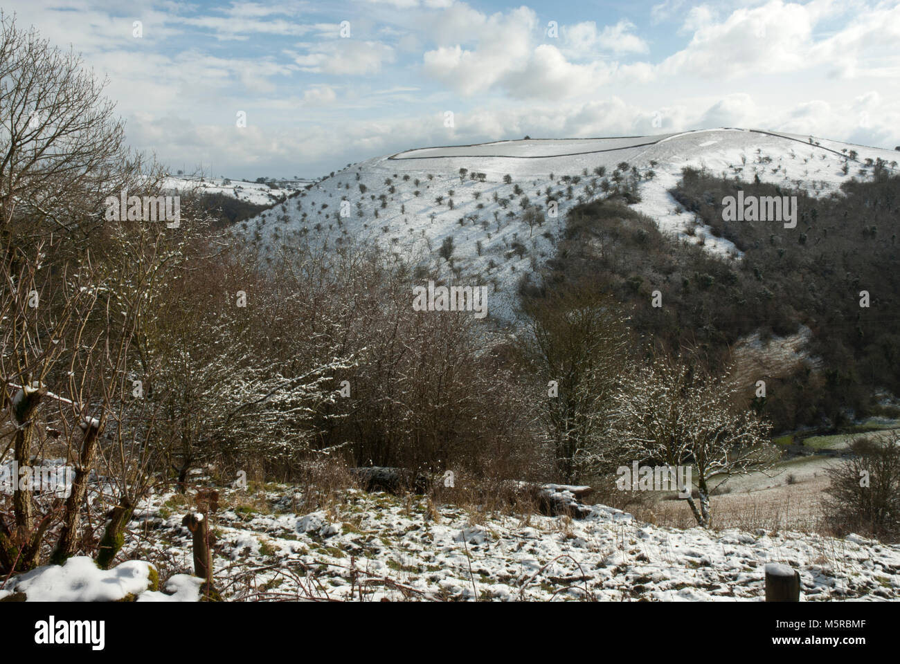 Winters landscape. Wintry view across Manifold valley / Wetton Valley in the snow to Ossums Hill. Blue sky, sunshine, Stock Photo
