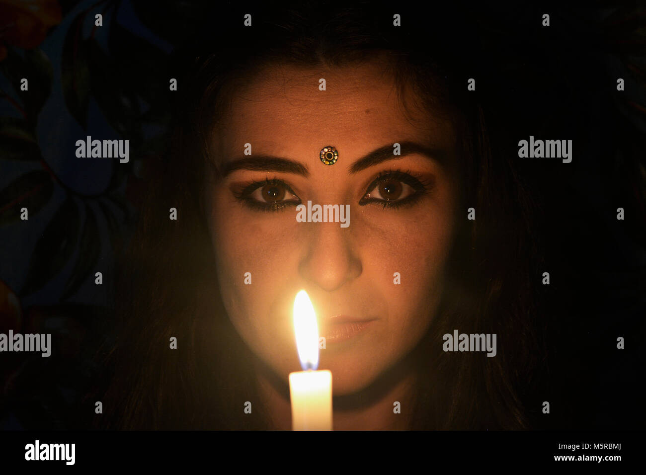 Woman's face with candle in the dark - Stock Image