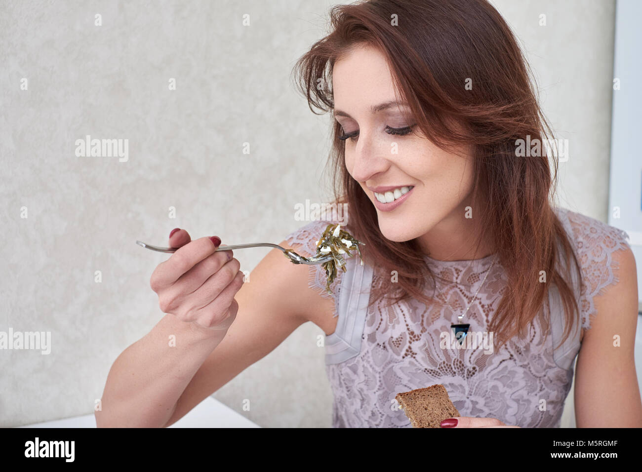Portrait of beautiful young woman having healthy breakfast in the kitchen. - Stock Image