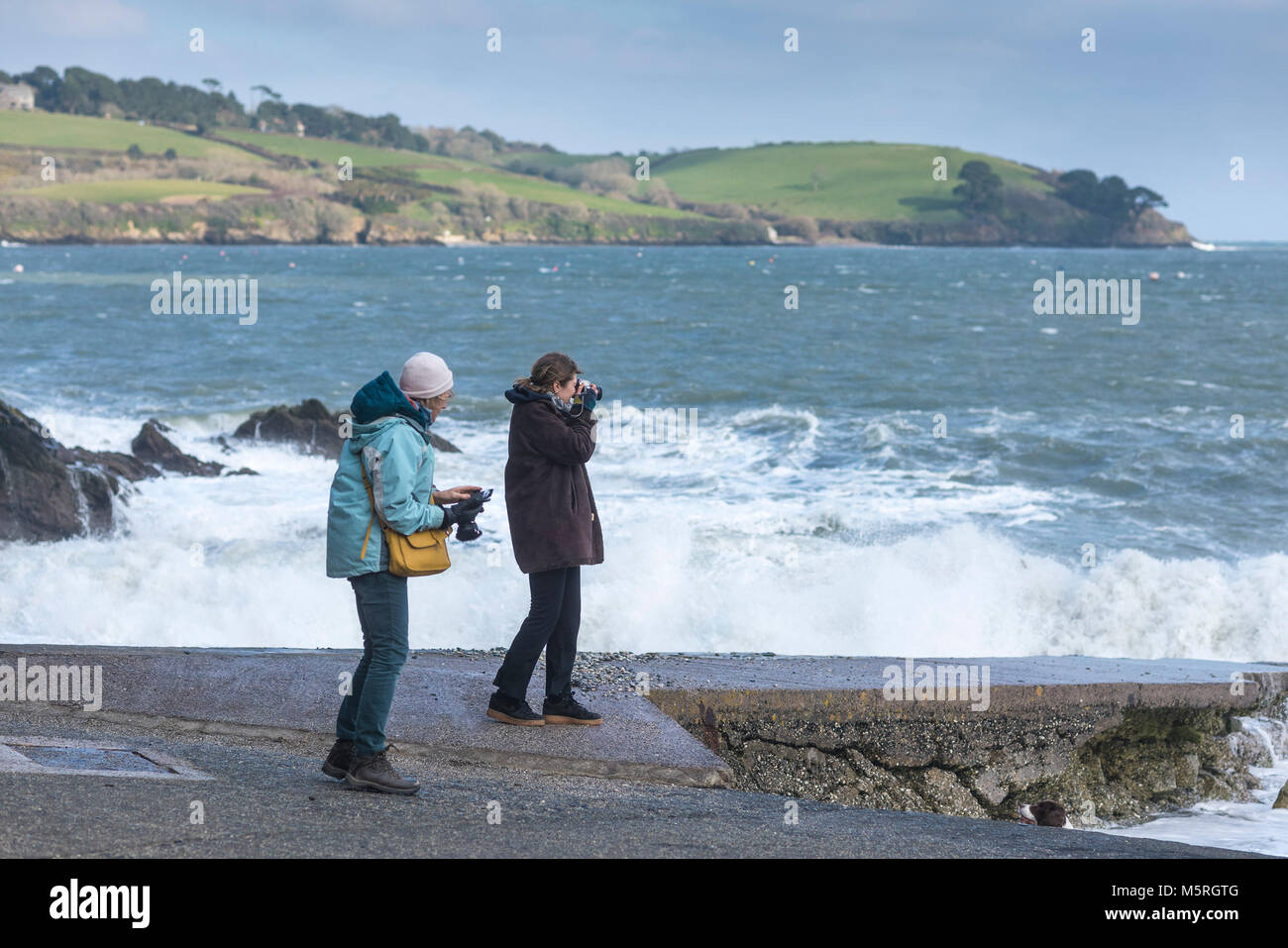 Tourists taking photographs on the beach at Trebah Garden Gardens in Cornwall. - Stock Image