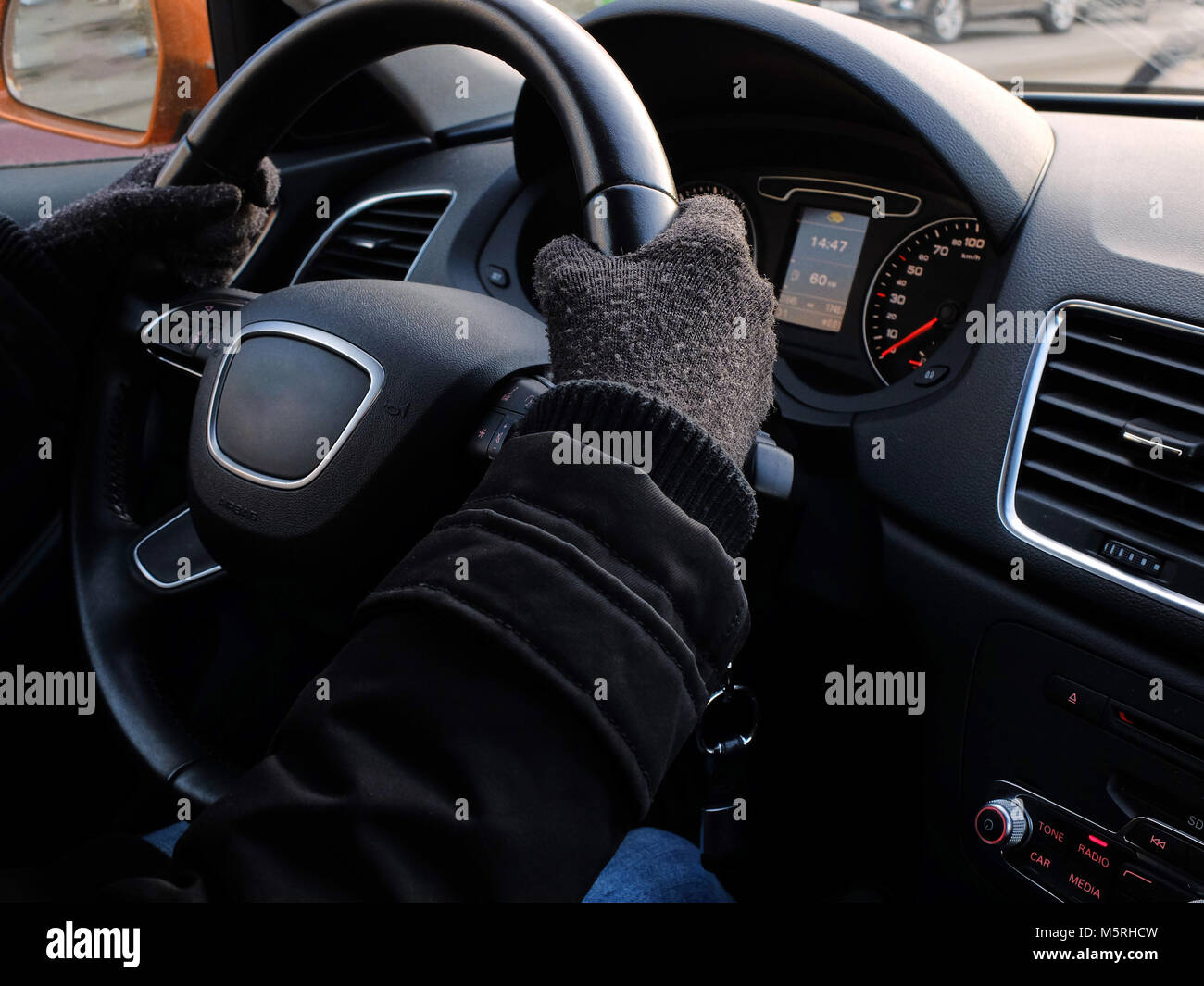 Female hands in the gloves on the steering wheel of expensive car - Stock Image