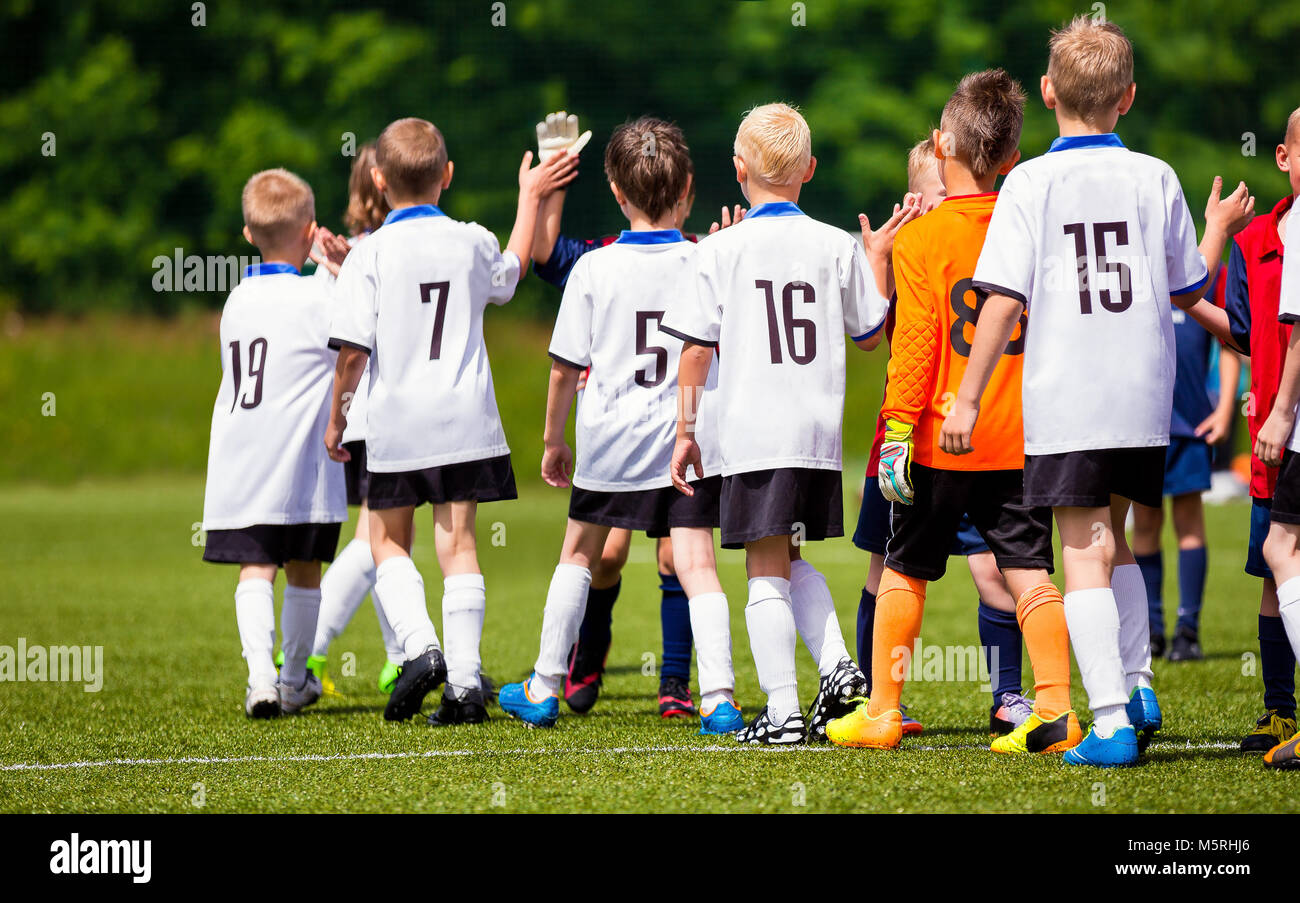 Happy Football Players Giving High Five At Field. Soccer Players High Five After Game. Two Teams High Five After - Stock Image