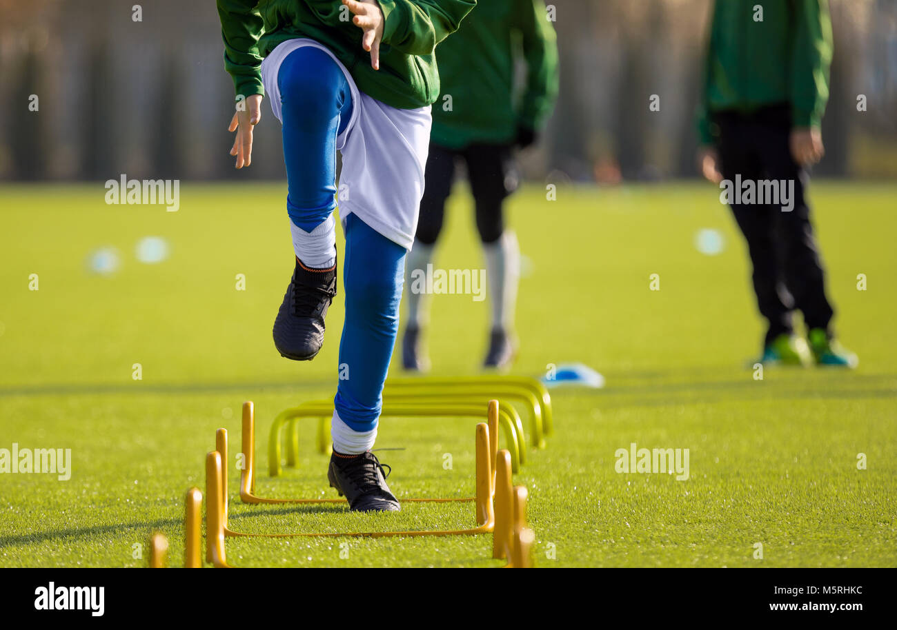 Boy Football Player In Training with Ladder. Young Soccer Players at Training Session. Soccer Speed Ladder Drills - Stock Image