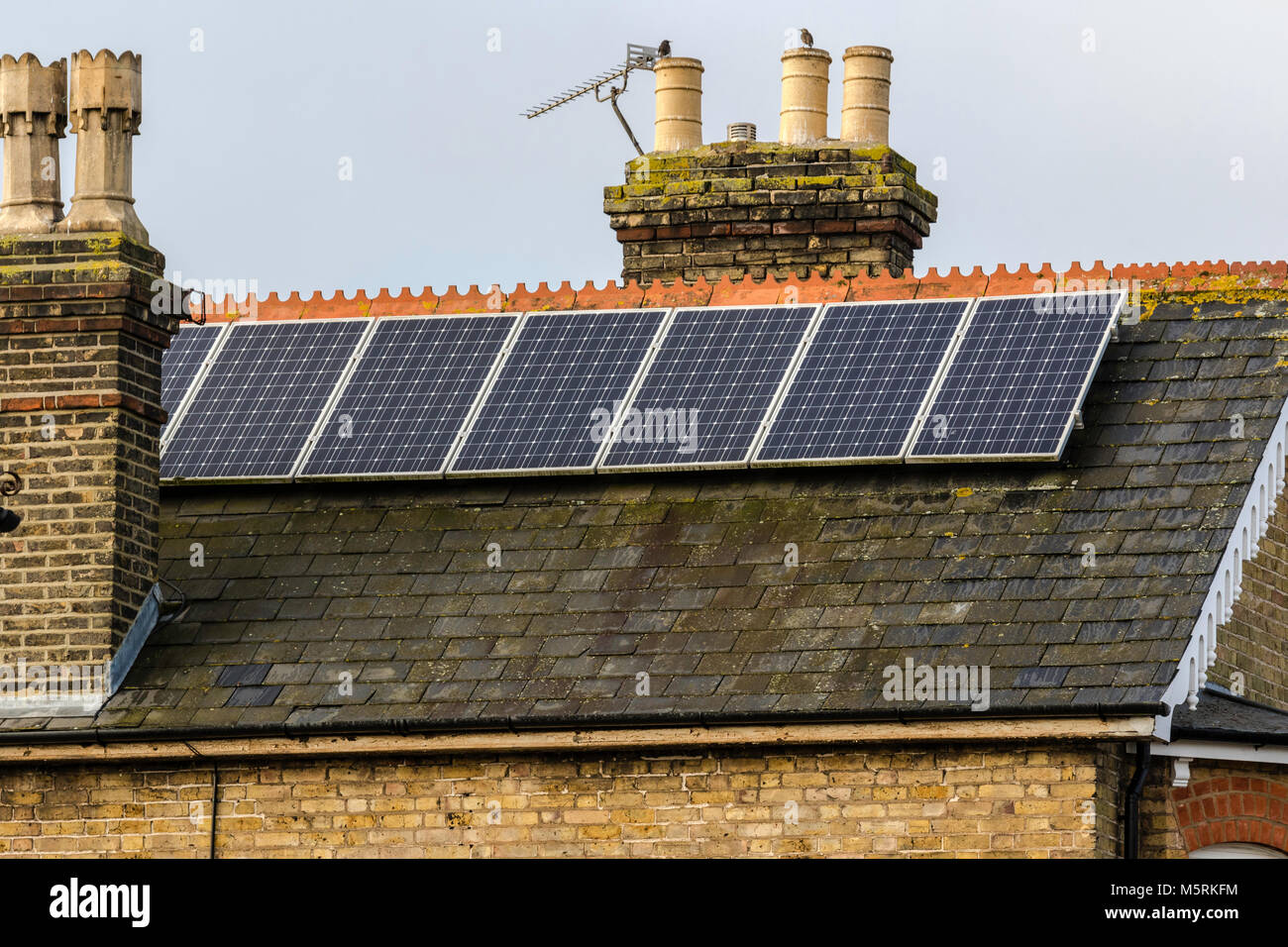 England. Solar power panels on slate roof, old brick house. Chimney pots on side and in middle. Two sources of energy. - Stock Image