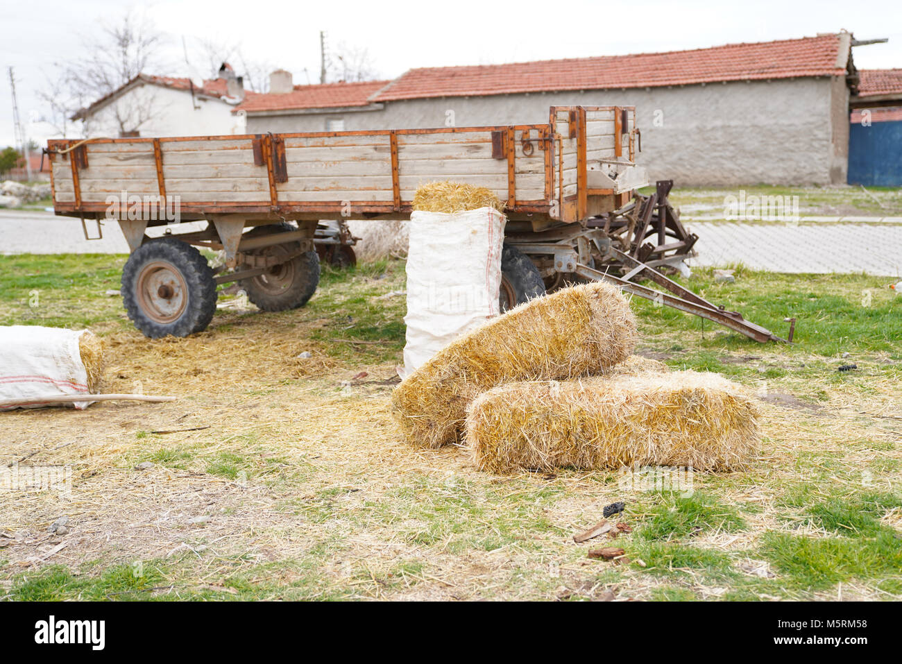 Several hay bales next to the tractor trailer and country houses and hayloft in background - Stock Image