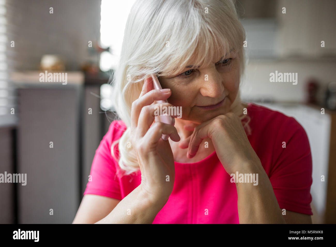 Portrait of pensive senior lady listening to phone conversation intently Stock Photo