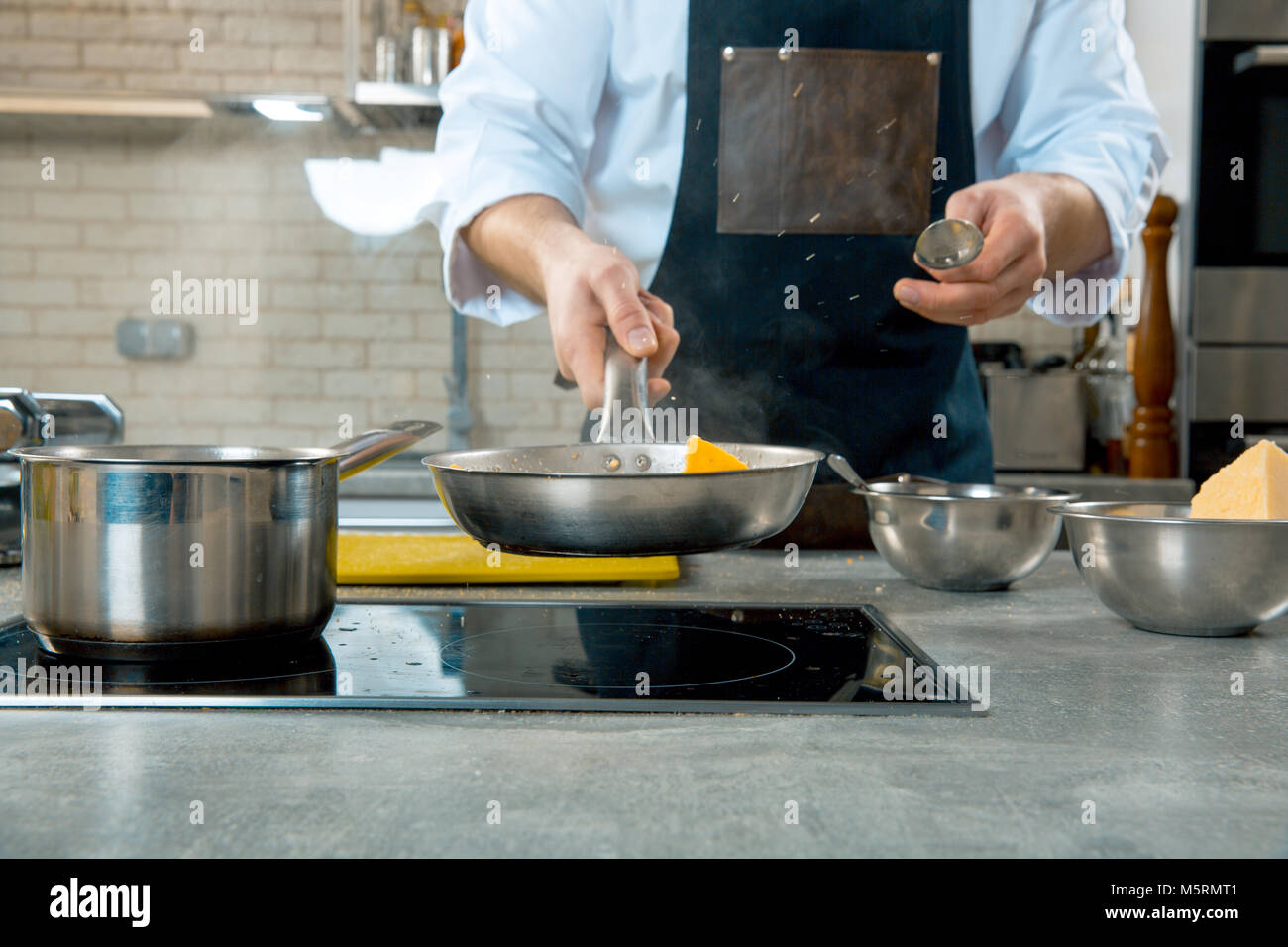Mid section of chef preparing food in the kitchen of a restaurant. the chef fry food in a frying pan - Stock Image