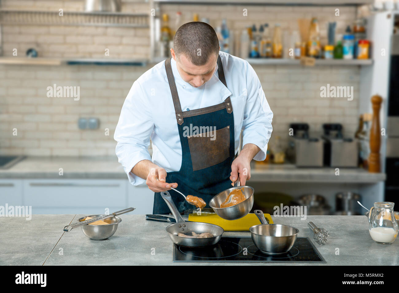Chef cook pours sauce into a frying pan. Fast food dinner and lunch restaurant bar. Kitchen interior - Stock Image