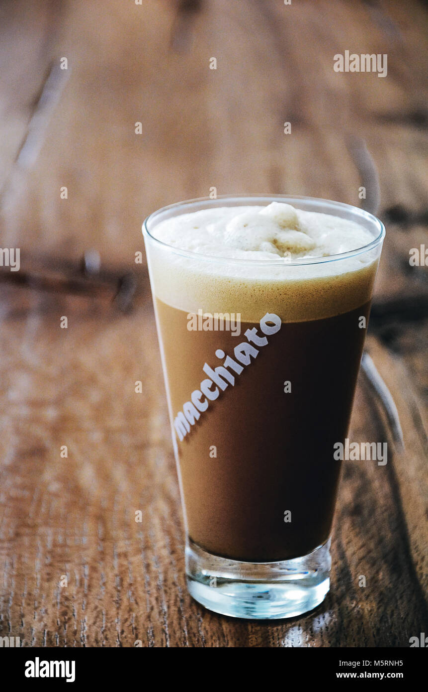 Latte macchiato long glass with word Macchiato written standing on wooden Background - Stock Image