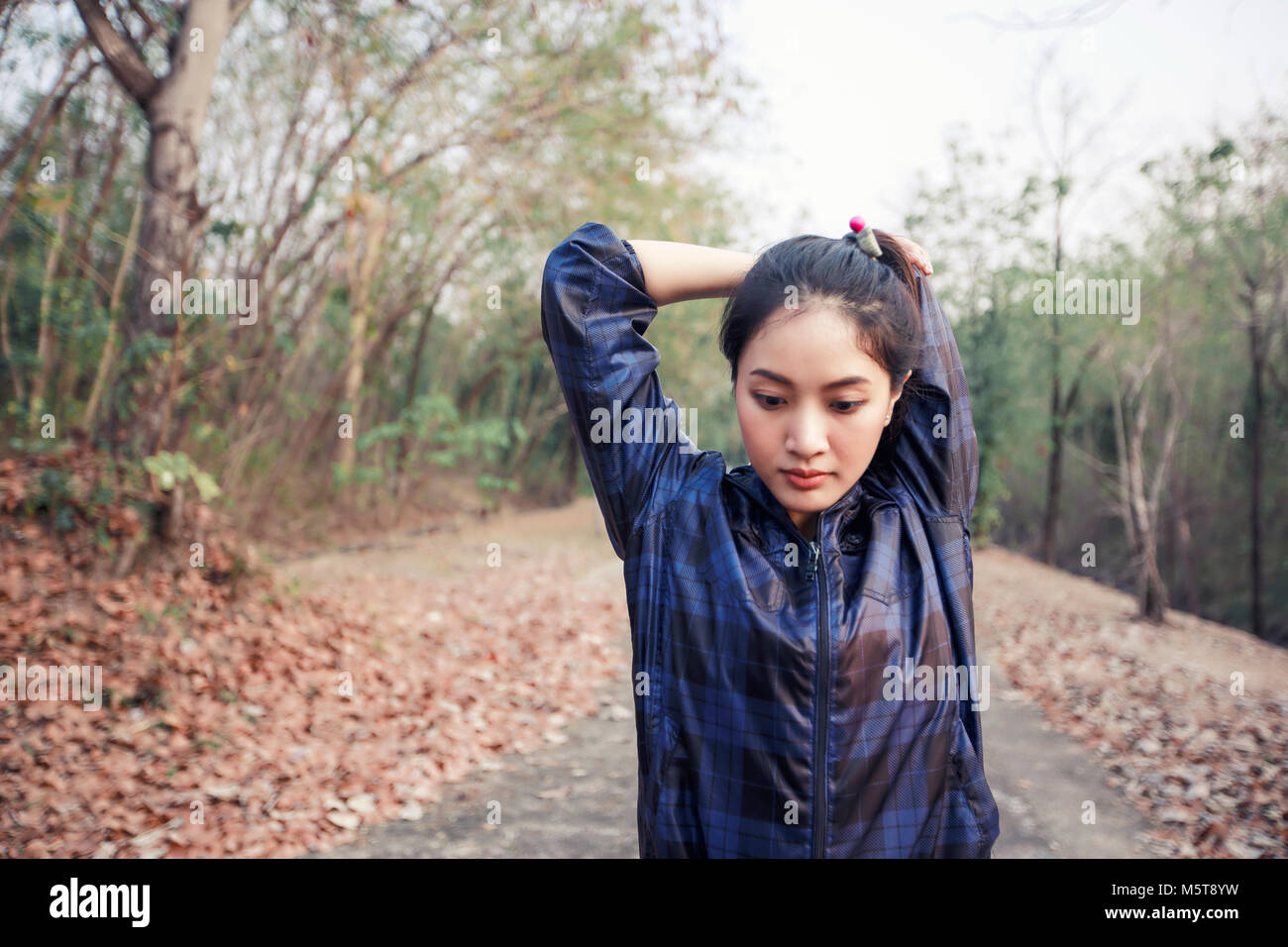 Athletic woman asia warming up and Young female athlete exercising and stretching in a park before Runner outdoors, - Stock Image