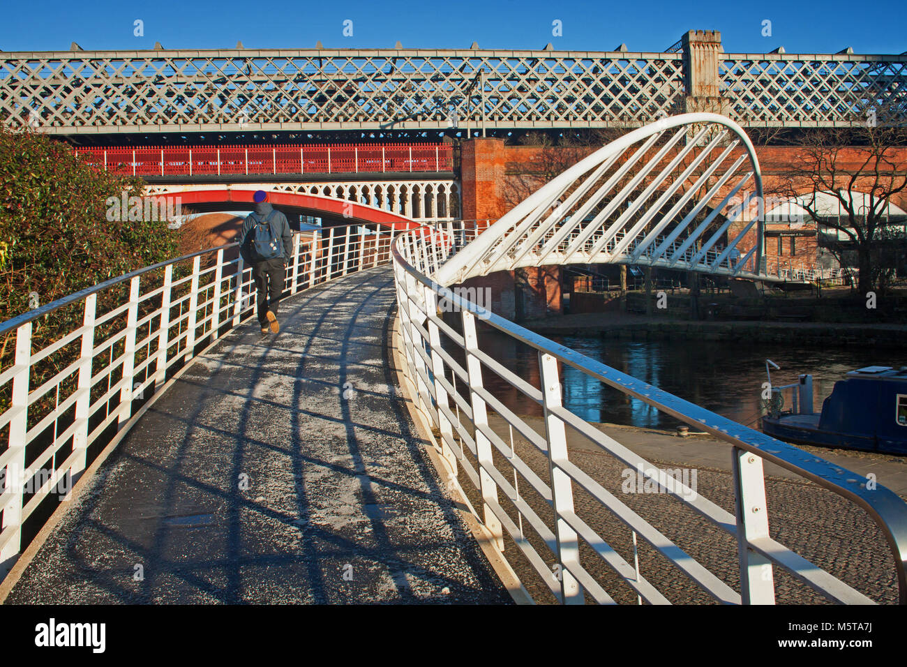 Crossing merchants' bridge at Castlefield, Manchester - Stock Image